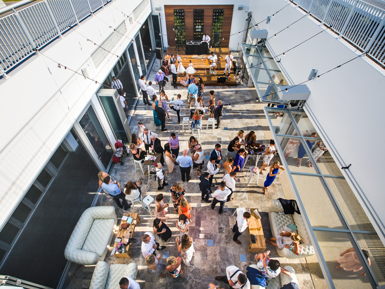 Top View Of The Function Room Extension With String Lights, Couch, Tables, Wooden Plant Wall In Front And People Gathering