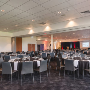 Tables And Chairs In Banquet Style Setup Inside The Function Room With Projection Screen In Front