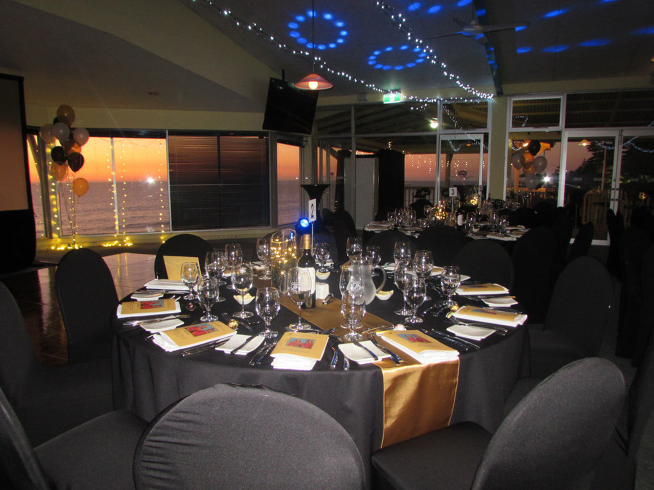 Chairs And Tables In Banquet Style With Lights And Balloons Inside The Function Room With Ocean View In Dusk