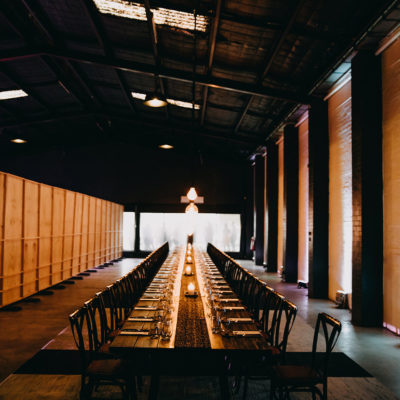 A Long Table With Chairs Inside The Function Room With Warm Hanging Lights