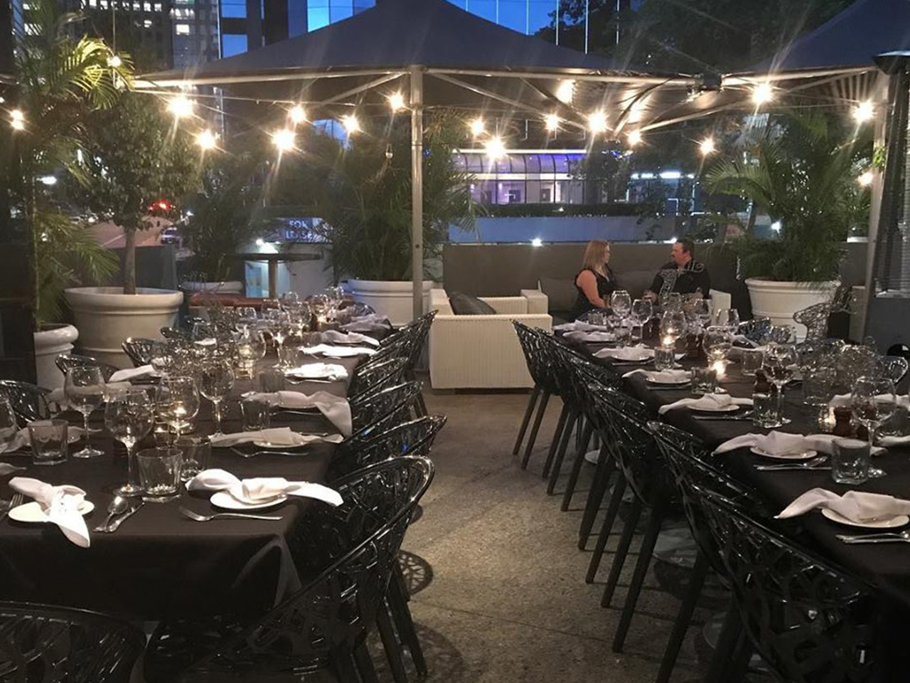 Function Area With Chairs And 2 Long Tables With Hanging Lights