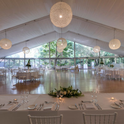 Chairs And Tables In Banquet Style With A Long Table Inside The Marquee With Flower Centerpieces, Chandeliers