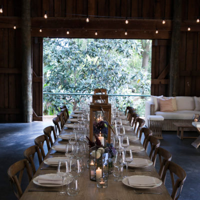 Chairs And A Long Table Setup Inside The Barn With A Couch Behind And The Back Door
