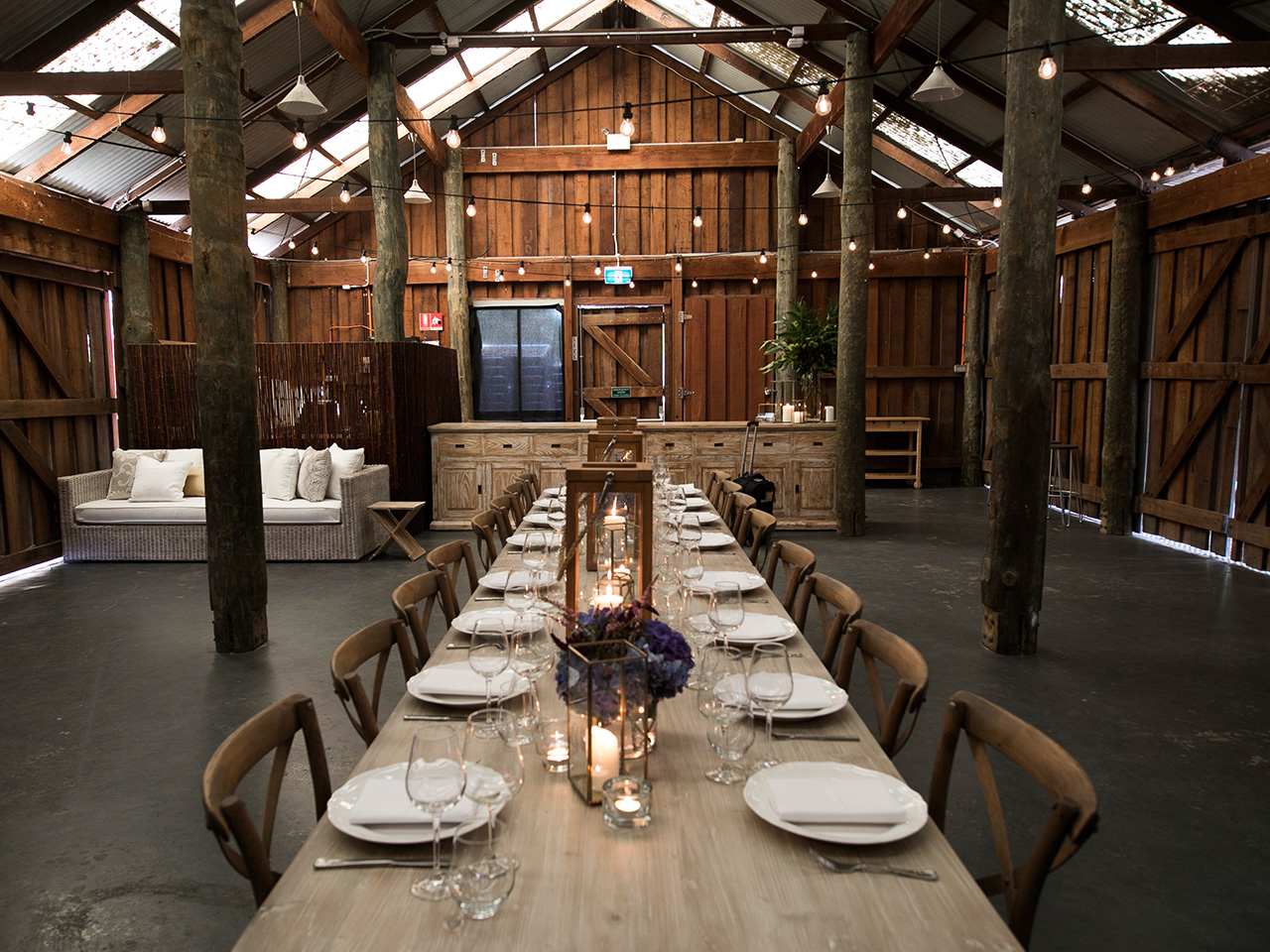 Chairs And A Long Table Setup Inside The Barn With A Couch And A Rectangular Cabinet Behind
