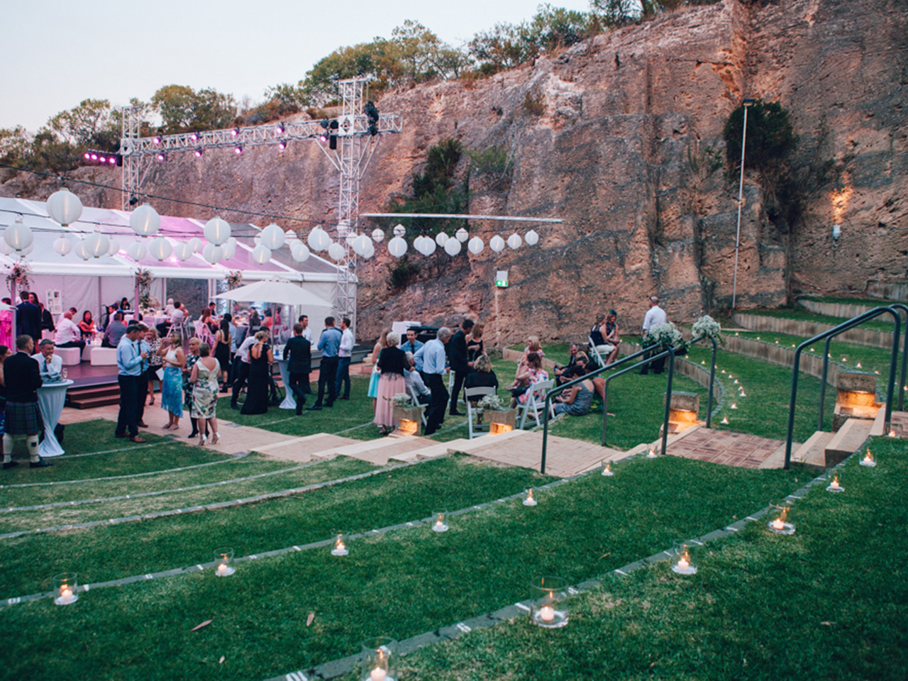 People Gathering Outside The Function Room In Dusk With Cocktail Tables And Round Hanging Lights