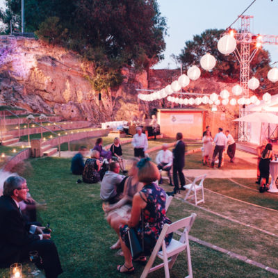 People Gathering Outside The Function Room In Dusk With Chairs And Cocktail Tables And Round Hanging Lights