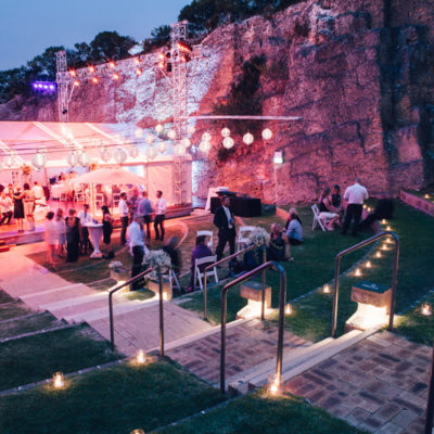 People Gathering Outside The Function Room In The Evening With Cocktail Tables And Round Hanging Lights