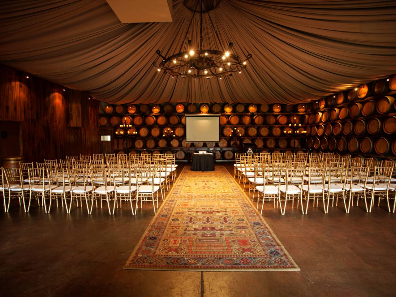Conference Setup Inside The Function Room With Wine Casks As Wall With Projection Screen And A Chandelier