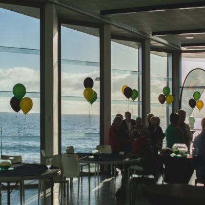 People Gathered Inside The Function Room With Round Tables, Chairs And Balloons