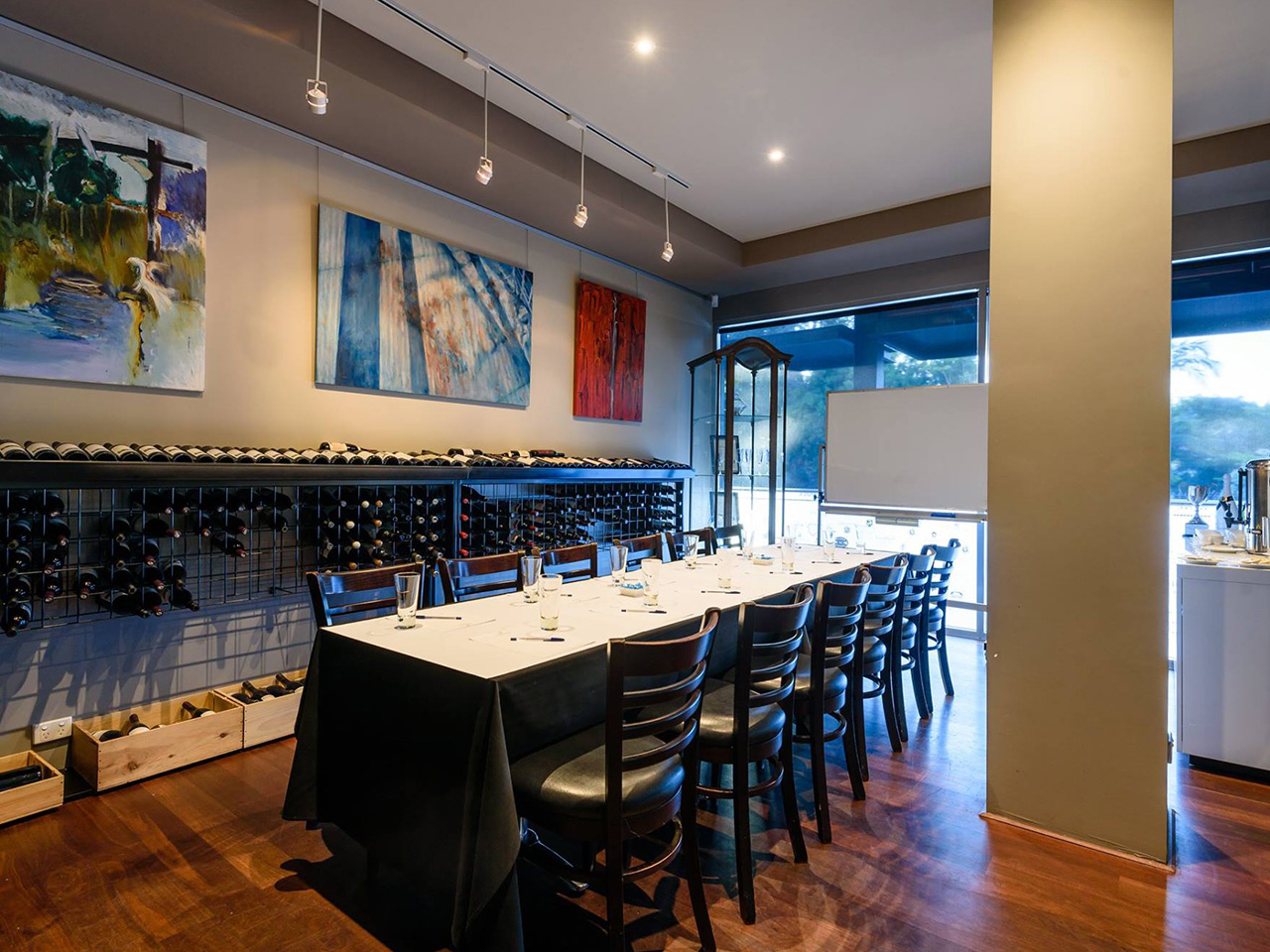 Chairs And A Long Table. With Wall Painting Behind, Wine Bottles And Outside View