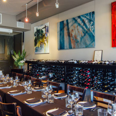 Chairs And A Long Table. With Wall Painting Behind And Wine Bottles