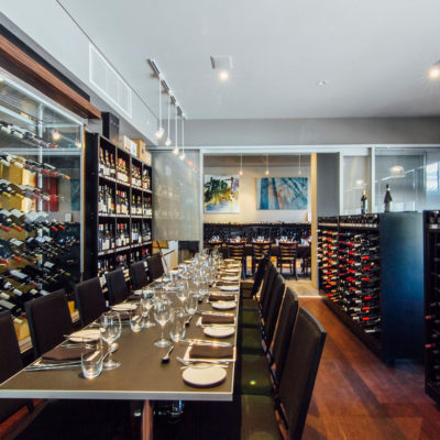 Inside The Bistro With Wine Bottles Everywhere And Long Tables
