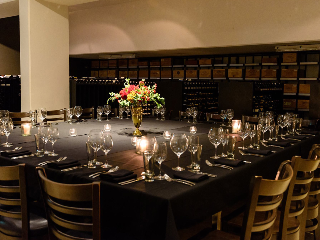 Chairs And A Square Table With Flower Centerpiece And Wine Glasses