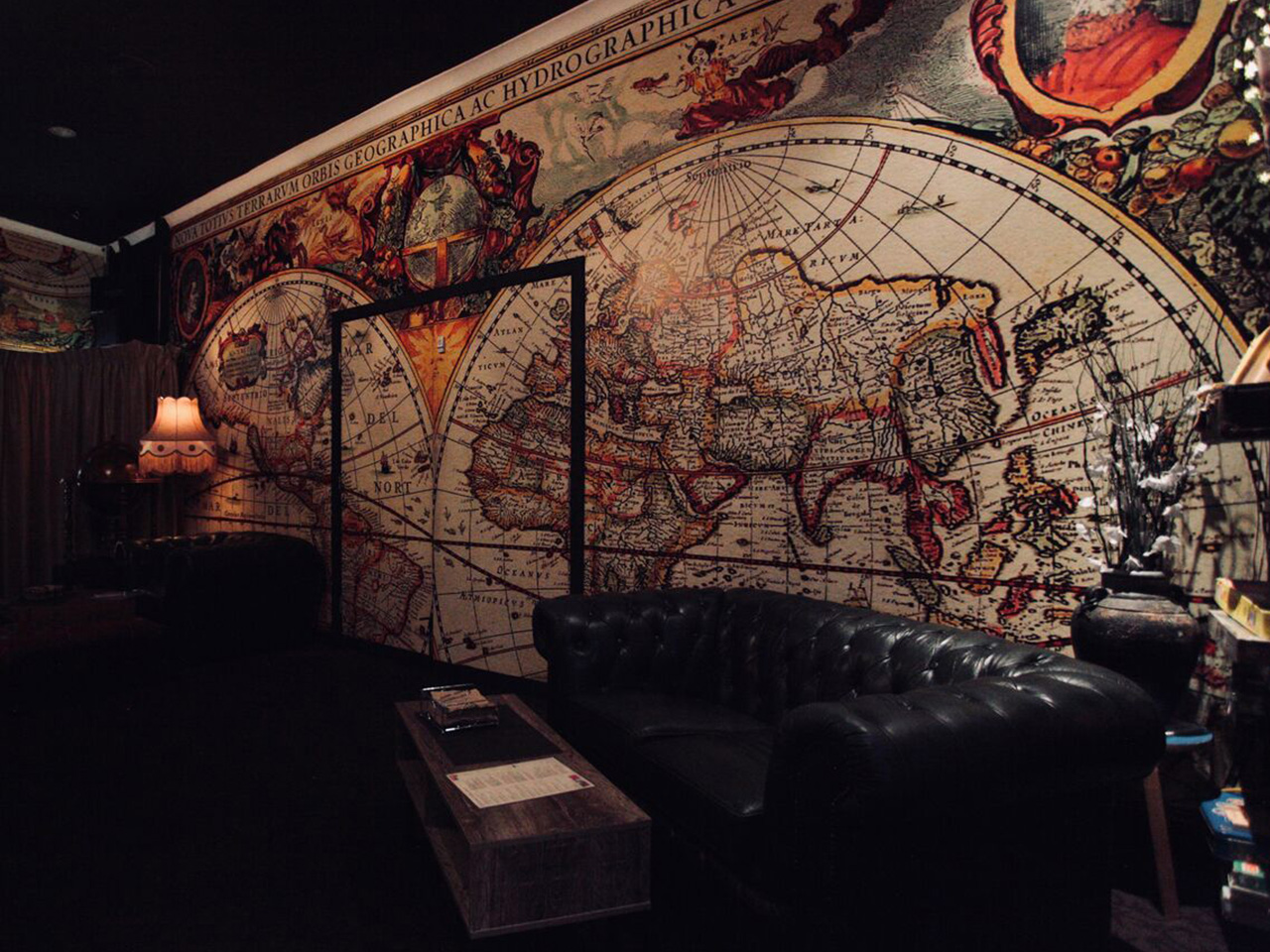 A Center Table, Couch And A Lamp On The Side With A World Map Design On The Wall