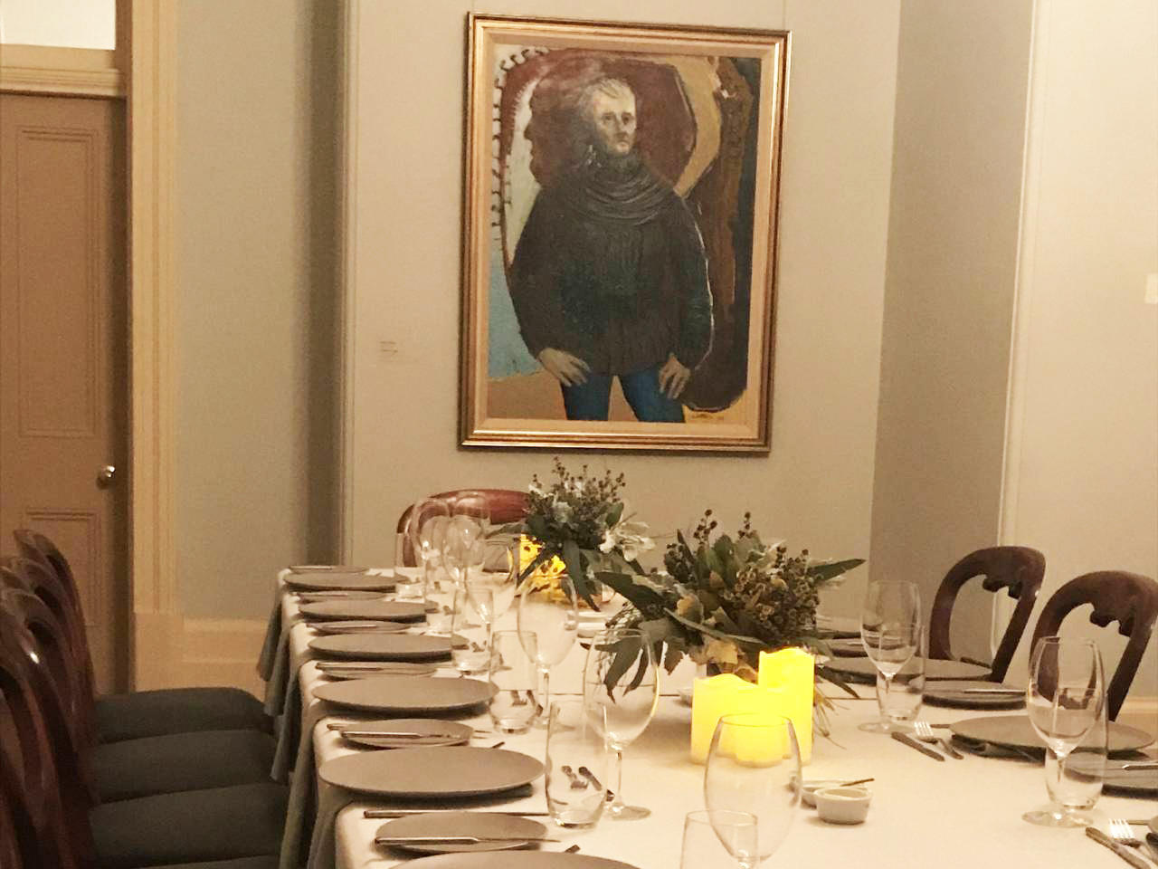 A Long Table With Chairs Setup For A Private Dinner With A Painting Of A Man In The Wall Inside The Function Room