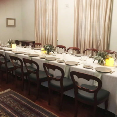 A Long Table With Chairs Setup For Private Dinner Inside The Function Room