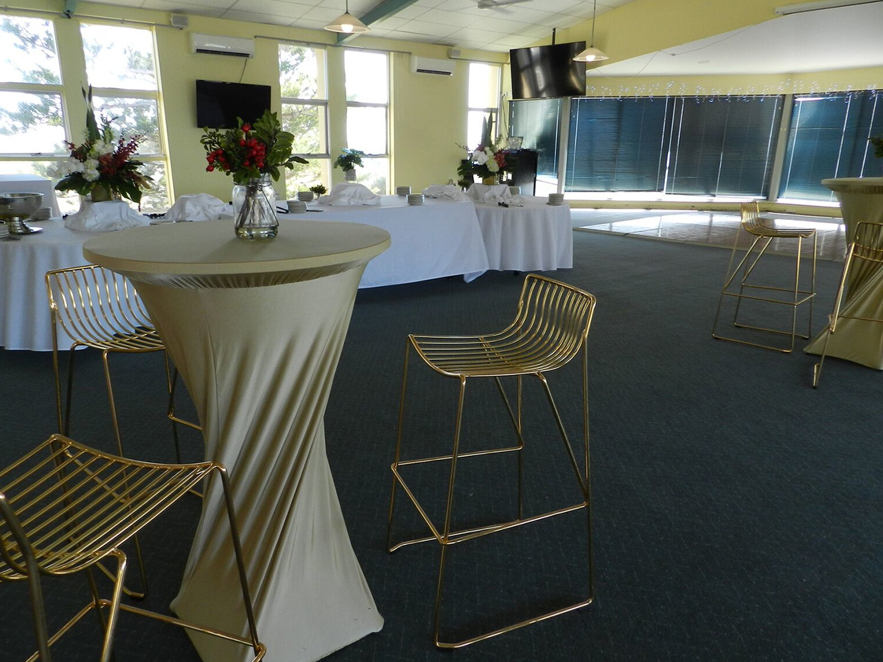 Cocktail Tables With High Chairs And A White Long Table Behind Inside The Function Room