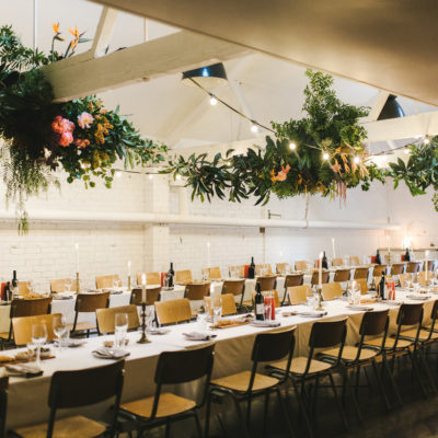 2 Long Tables Setup For An Event Inside The Function Room With Ceiling Flower Details