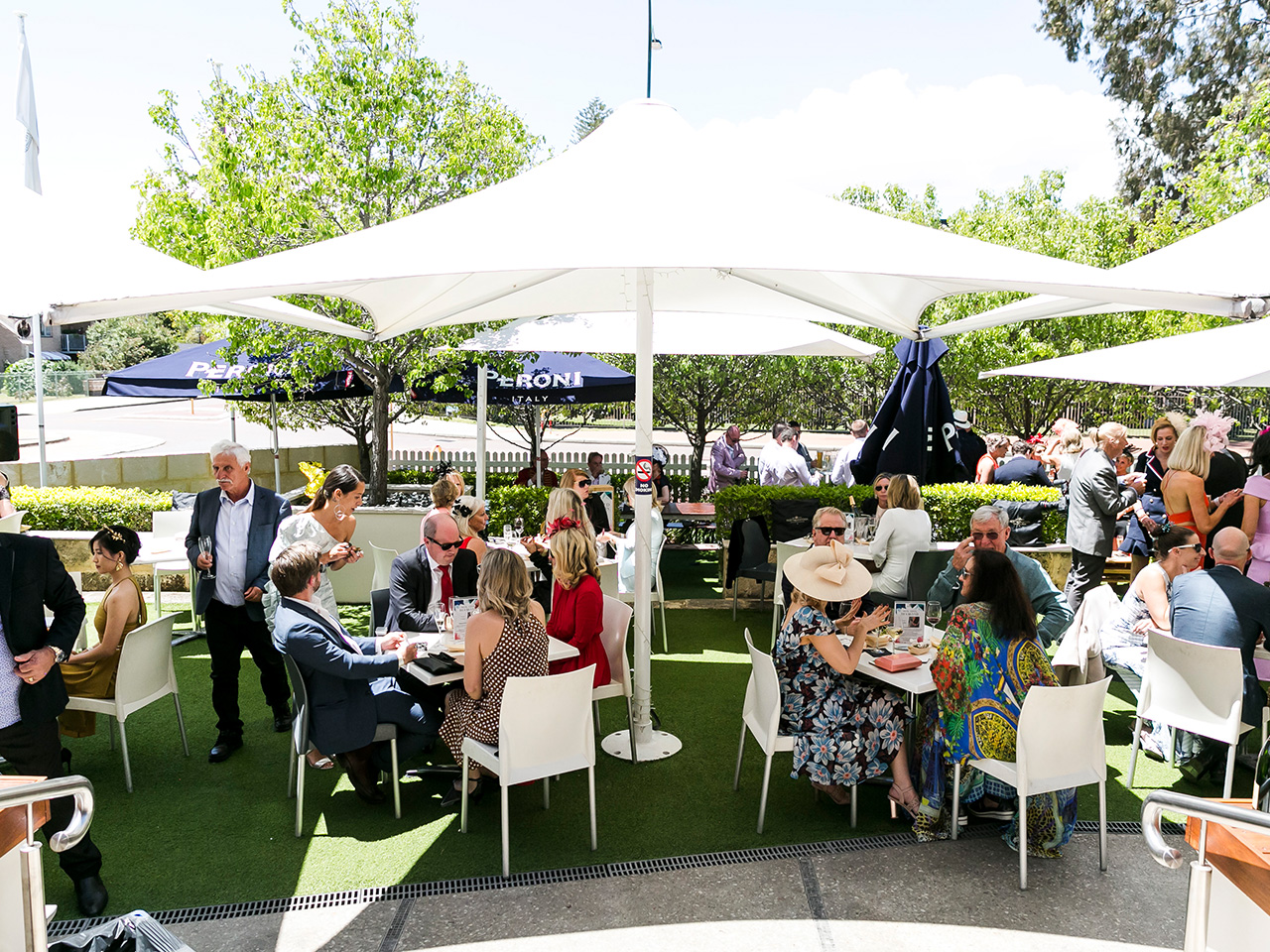 Guests Gathered Under The Open Function Area Shaded With Large Umbrellas