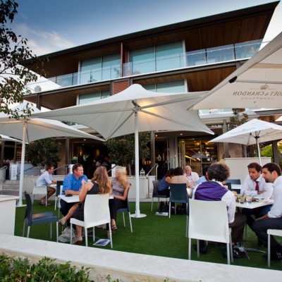 Guests Gathered Under The Open Function Area Shaded With Large Umbrellas In Dusk