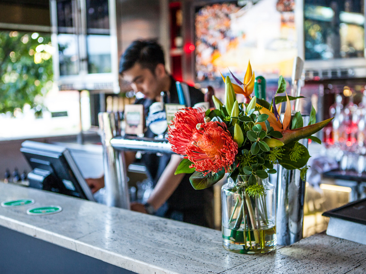 Bartender In The Mini Bar With Table Flower In A Vase