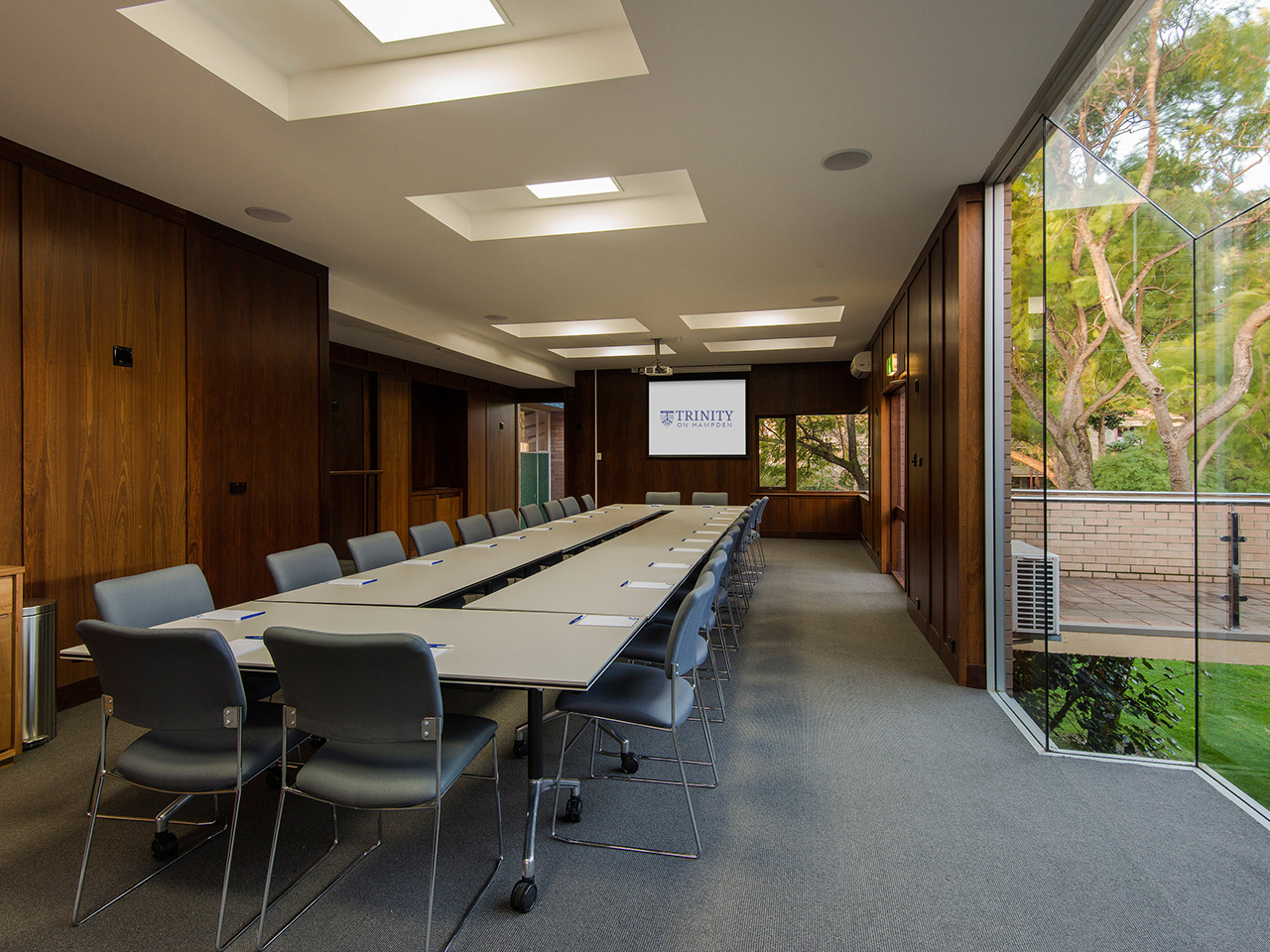 Tables And Chairs In Boardroom Setup Inside The Function Room With Projection Screen And Garden View