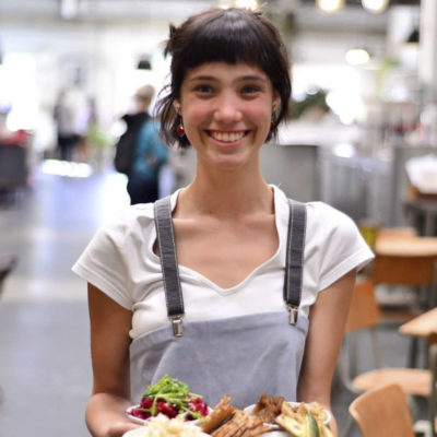 Young girl waitress facing camera service dishes of food with cafe in background