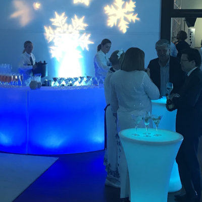 Few Guests Inside The Gallery With Cocktail Drinks, Tables And Snowflakes Lightning