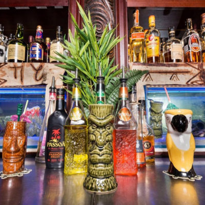 Tiki Table Top Designs Placed In The Table In Front Of The Liquors Shelve at The Party Venue