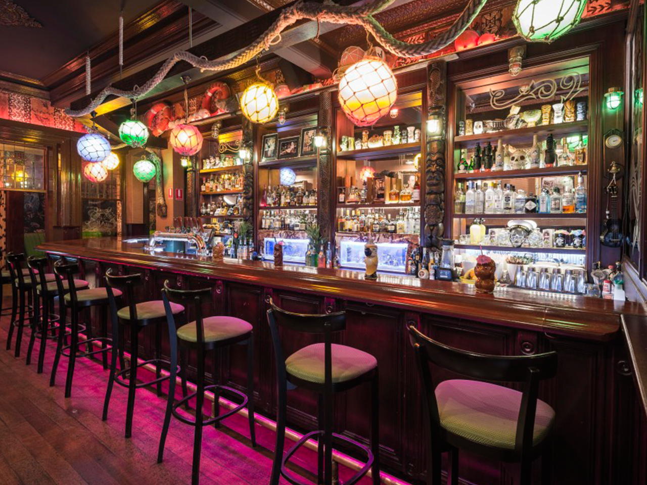 Inside The Party Venue Bar With High Chairs, Lanterns And Variety Of Liquors Displayed