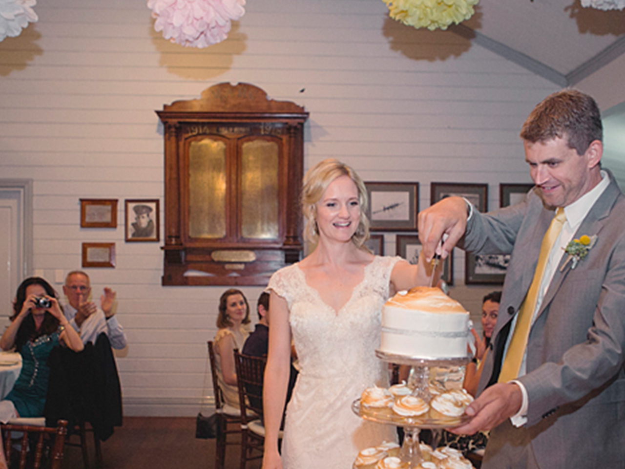 Groom And Bride Slicing Their Wedding Cake With Guests Behind Them