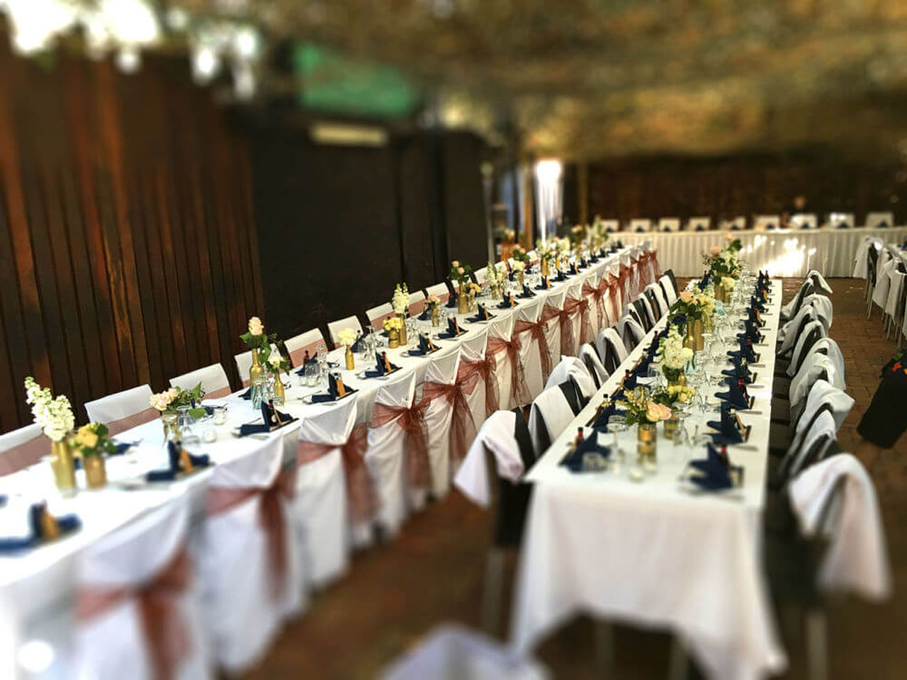 Long Tables Fully Set With Cutlery and Green Napkins In The Open Air Function Space