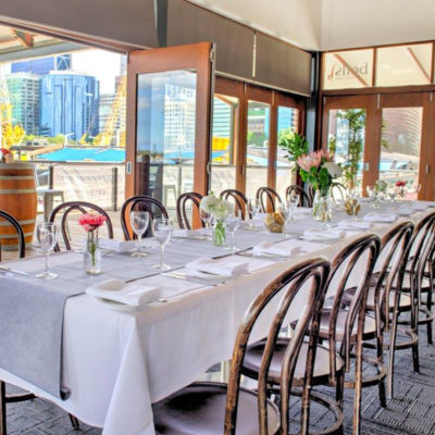 Chairs And Long Tables Setup For An Event Inside The Function Venue Perth With Glass Windows And A Balcony Behind