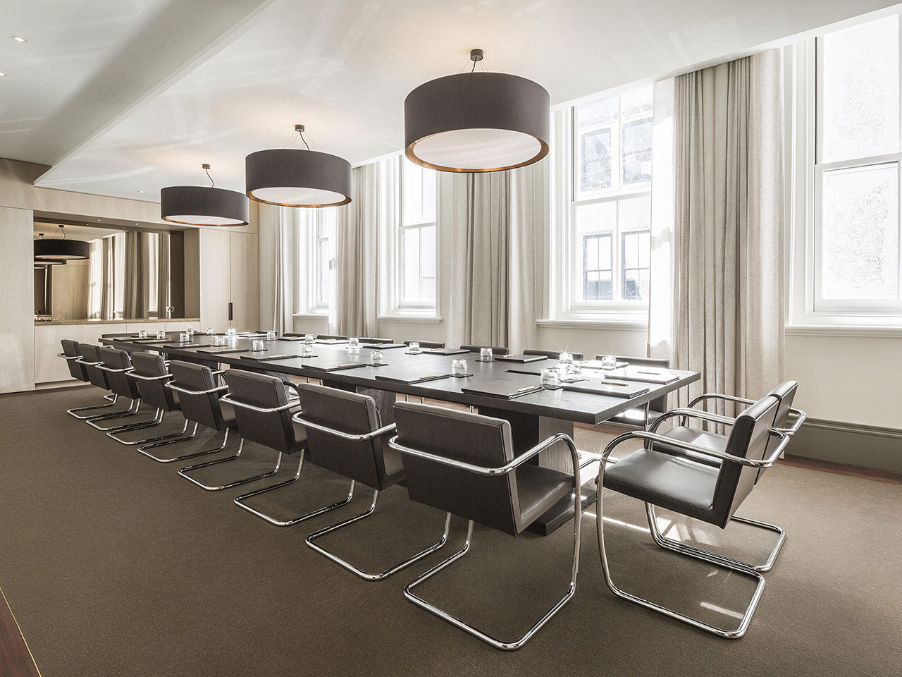 Chairs And Table Inside The Boardroom With Big Round Hanging Lights And Glass Windows