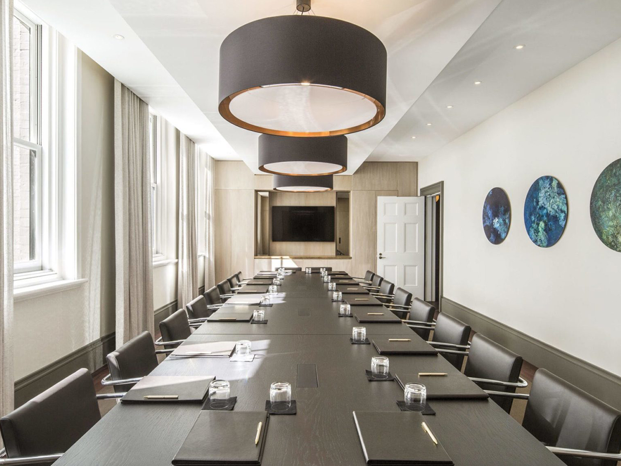 Chairs And Table Inside The Boardroom With Big Round Hanging Lights, Glass Windows And Round Wall Arts