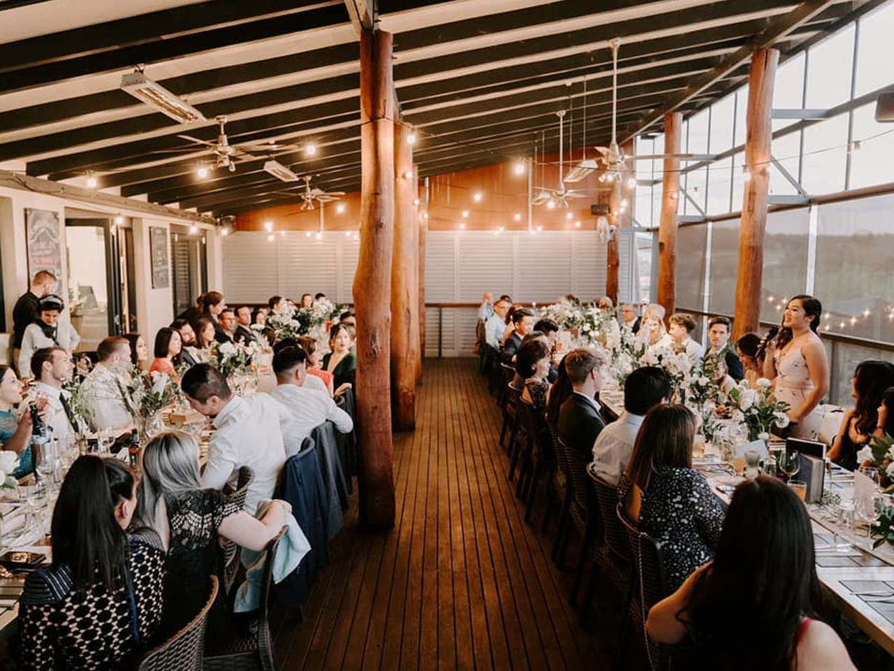 Guests Seated Inside The Function Room With Long Tables And Hanging Lights
