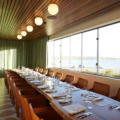 Two Tables And Chairs In Banquet Style Inside The Riverside Venue With Green Wall Curtain At The Back, Round Lights And Swan River Views