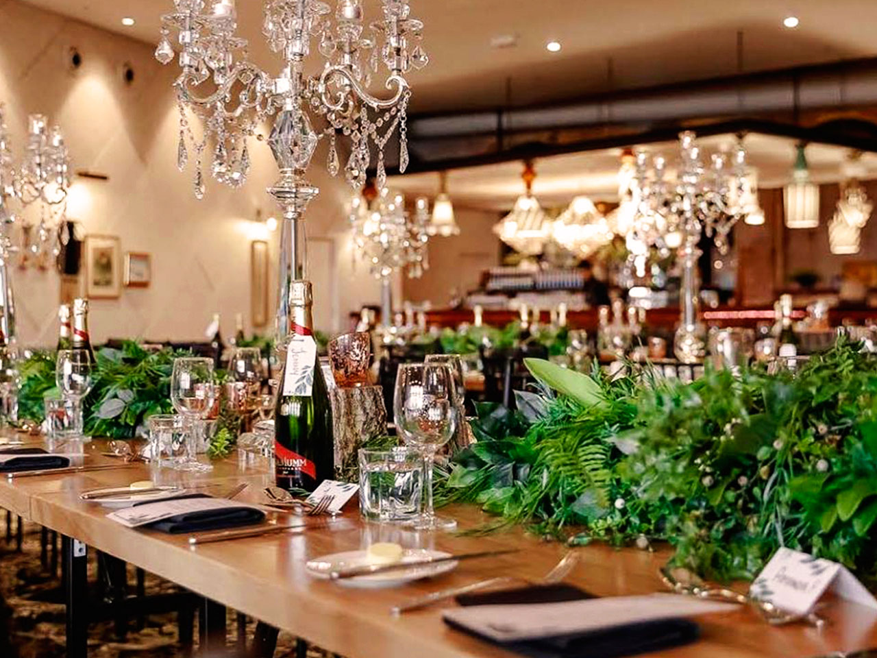 Long Tables And Chairs Setup For An Event With Table Centerpieces, Wines And Wine Glasses