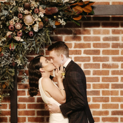 Bride and groom kissing under bouquet