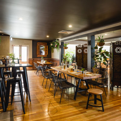 High Tables And Chairs With Regular Tables And Chairs On The Other Side And Indoor Hanging Plants Inside The Function Room