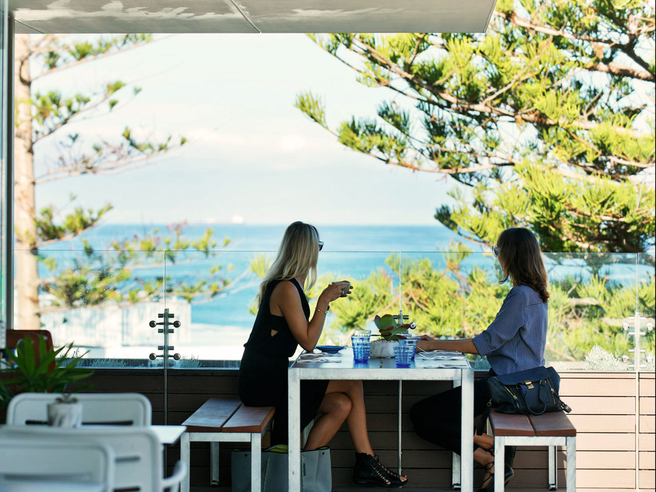 2 Women Sitting And Enjoying The Ocean View