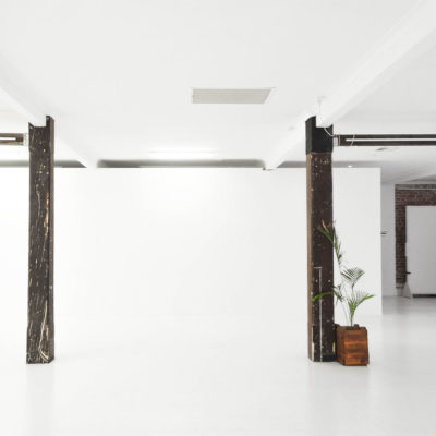 white gallery wall with wooden columns