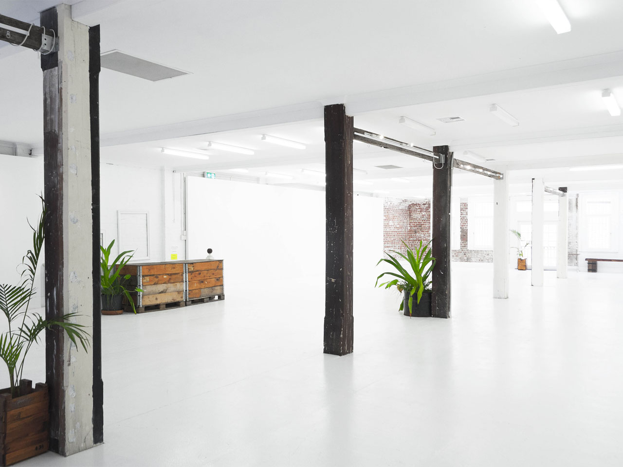 open gallery space with wooden columns