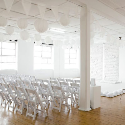 wedding setting with white chairs, awnings and brick work