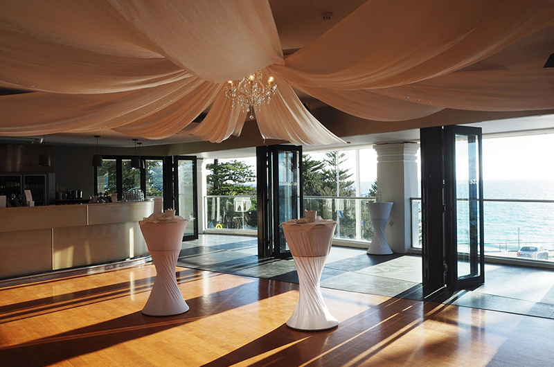 Large Venue With High Tables For Cocktail Style Function With Open Windows And Balcony With Ocean Views