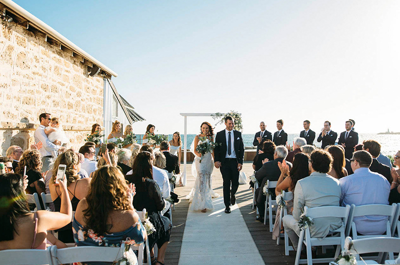 Newly Married Couple Walking Down The Aisle At Outside Courtyard Venue With Ocean in The Background