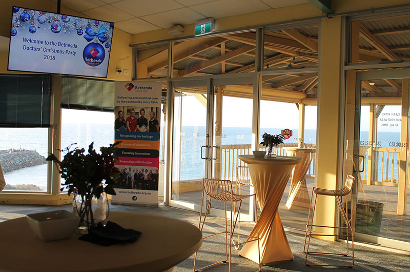 Tables and Chairs Set Up at a Venue Ready for a Corporate Function. Glass Windows Reveal The Ocean Backdrop
