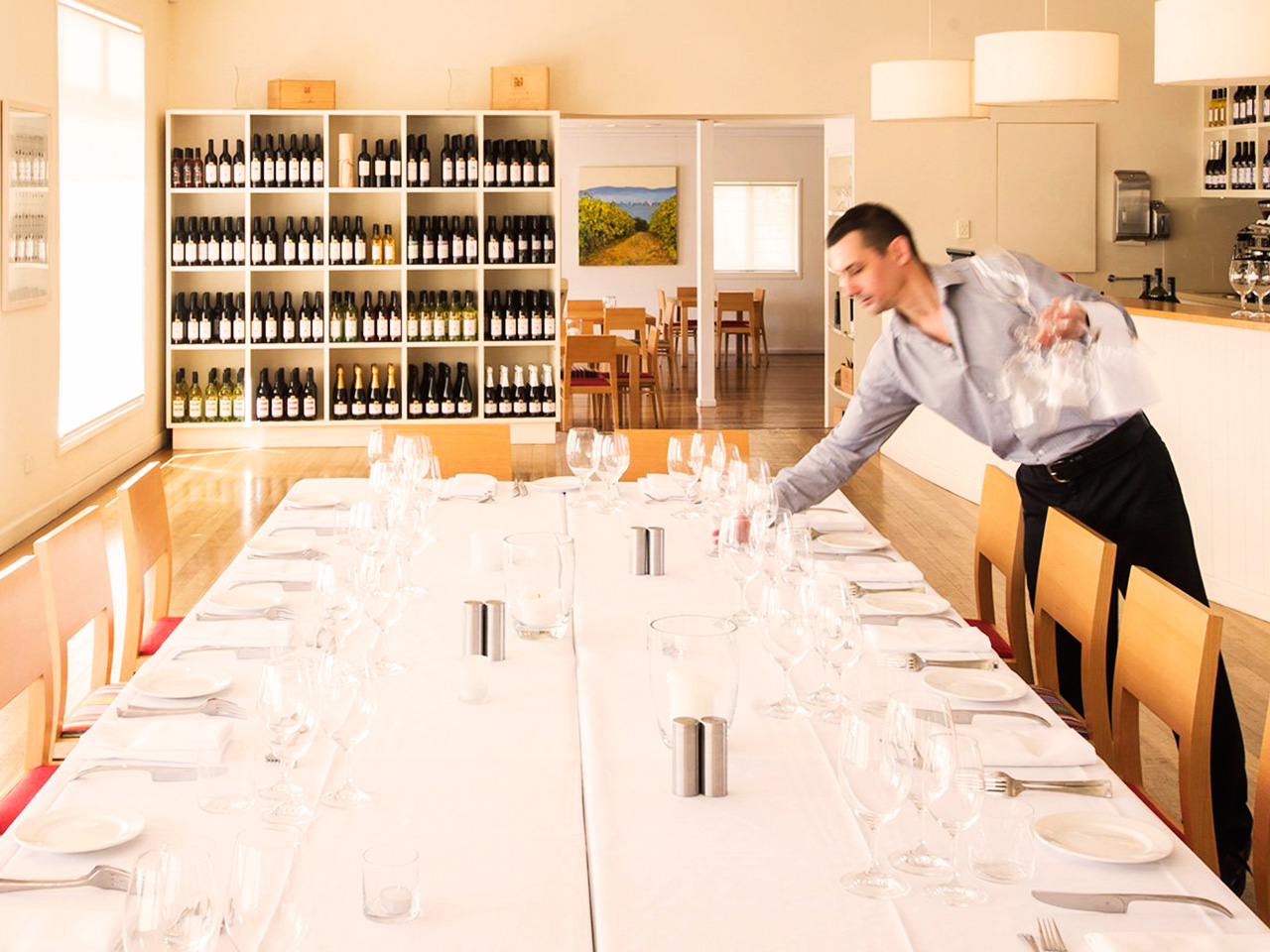 Man Setting Up The Long Table With Chairs And Wines On The Corner