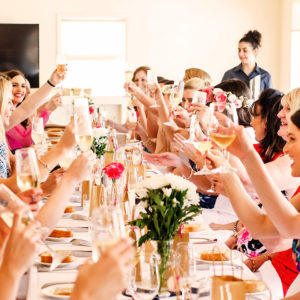 Guests Enjoying Their Drinks While Sitting On The Long Table