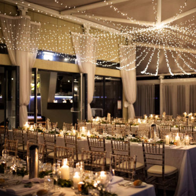 Long Tables With Chairs And String Lights Inside The Function Room